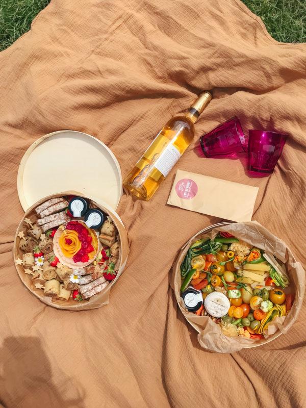 Boîte Brunch et Flore sur une couverture de pique-nique Atelier Woodie, accompagnées d'une bouteille de vin blanc et de verres, au parc Borély.